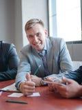 年轻可爱的商人谈话与同事在办公室 到达天空的企业概念金黄回归键所有权 免版税库存图片
