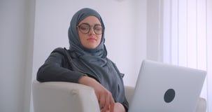 年轻可爱的回教与看照相机的膝上型计算机的女实业家和玻璃特写镜头画象hijab的参加  股票视频