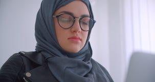 年轻可爱的回教使用看照相机的膝上型计算机的女实业家和玻璃特写镜头画象hijab的 股票录像