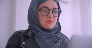 年轻可爱的回教使用看照相机的膝上型计算机的女实业家和玻璃特写镜头画象hijab的 股票视频