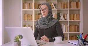 年轻可爱的回教使用膝上型计算机和饮用的咖啡的女实业家和hijab特写镜头画象玻璃的  影视素材