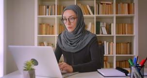 年轻可爱的回教使用膝上型计算机的女实业家和hijab特写镜头画象玻璃的在户内图书馆里 股票视频