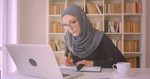 年轻可爱的回教使用采取笔记的膝上型计算机的女实业家和hijab特写镜头画象玻璃的在图书馆里 影视素材