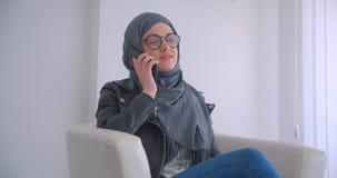 年轻可爱的回教女实业家和玻璃特写镜头画象hijab的谈话在坐在的电话 股票录像