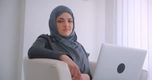 年轻可爱的回教女实业家特写镜头画象hijab的和有看照相机的膝上型计算机的坐在  影视素材