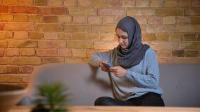 年轻可爱的回教女性特写镜头射击发短信在电话的hijab的,当坐长沙发户内在舒适时 影视素材