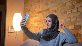 年轻可爱的回教女性特写镜头射击采取在电话的hijab的selfies,当坐长沙发户内时 股票视频