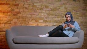 年轻可爱的回教女性特写镜头射击hijab传讯的在电话,当休息松弛在长沙发时 影视素材