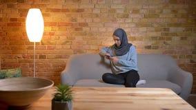年轻可爱的回教女性特写镜头射击hijab的使用电话,当坐长沙发户内在舒适家时 股票录像