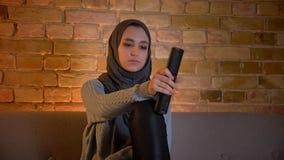 年轻可爱的回教女性特写镜头射击hijab看着电视和对负的遥控,当坐时 股票录像