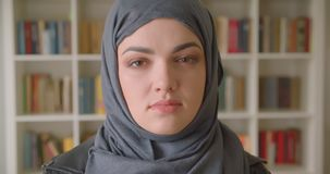 年轻可爱的回教女生特写镜头画象看照相机的hijab的在大学图书馆里户内 影视素材