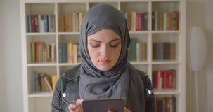 年轻可爱的回教女生特写镜头画象hijab的使用看照相机的片剂在学院 股票录像