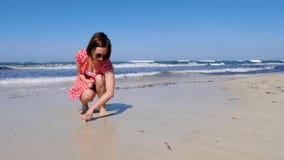 年轻可爱的在一个偏僻的沙滩的妇女画的心脏标志与击中岸的强的波浪 她佩带红色礼服和太阳 股票录像