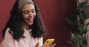 年轻可爱的在她的智能手机和有乐趣的女孩读的喜讯坐床 她唱歌,跳舞,高兴 股票视频