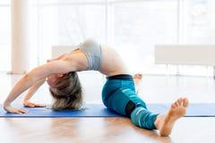 年轻可爱的女子实践的瑜伽佩带的运动服,绿色裤子,灰色胸罩,室内全长 图库摄影