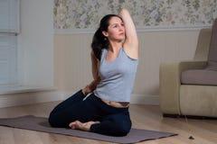 年轻可爱的女子实践的瑜伽,佩带的运动服,凝思会议,家内部 免版税库存图片