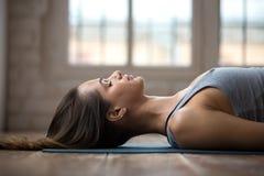 年轻可爱的女子实践的瑜伽,做尸体,接近的u 库存图片
