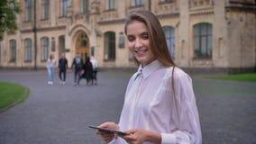 年轻可爱的女学生在她的片剂工作在夏天,微笑,观看对照相机,通信概念 股票录像