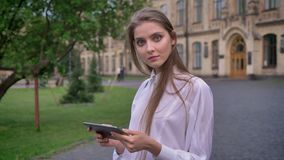 年轻可爱的女学生在她的片剂工作在夏天,观看在照相机,通信概念 影视素材