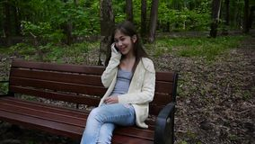 年轻可爱的女孩与在长凳的电话讲话 在公园空白夏天的结构树的云彩 微笑 射击静态照相机的HD录影镜头 股票视频