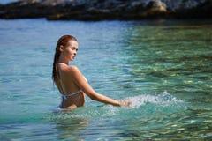 年轻可爱的女孩享受热的夏日在海滩 免版税库存图片