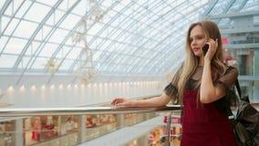 年轻可爱的女孩去购物在购物中心,谈话在电话,购物的概念,时尚概念,通信概念 股票视频