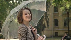 年轻可爱的女孩在有伞的公园走自白天,在夏天,微笑,观看对照相机 影视素材
