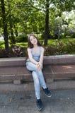年轻可爱的女孩坐长凳 在公园空白夏天的结构树的云彩 微笑 照片 库存照片