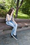 年轻可爱的女孩坐长凳 在公园空白夏天的结构树的云彩 微笑 照片 免版税库存图片