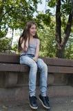 年轻可爱的女孩坐长凳 在公园空白夏天的结构树的云彩 微笑 照片 库存图片