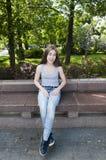 年轻可爱的女孩坐长凳 在公园空白夏天的结构树的云彩 微笑 照片 图库摄影