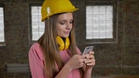 年轻可爱的女孩建造者发短信给在她的智能手机的消息,通信概念 股票录像