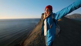 年轻可爱的女孩徒步旅行者沿含沙壁架或海边峭壁去 举他的手,神色在金黄 股票录像