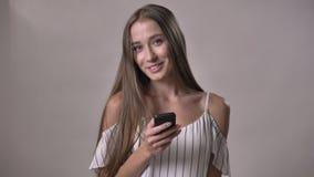 年轻可爱的女孩拿着智能手机,观看在照相机,微笑,通信概念,灰色背景 股票视频