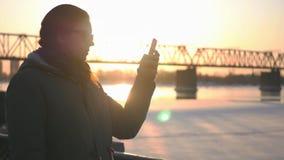 年轻可爱的女孩沿一座铁路桥和美好的日落的背景的江边走 库存图片