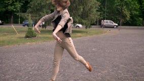 年轻可爱的女孩跳舞自白天,在夏天,行动用手,运动概念 股票录像