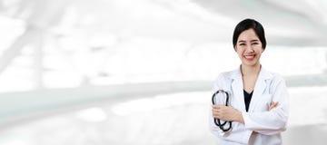 年轻可爱的女性亚裔医生或医师画象横渡了医疗武器储备的听诊器 库存图片