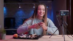 年轻可爱的女性博客作者特写镜头射击有dreadlocks放出活和给的化妆用品做广告与氖 股票视频