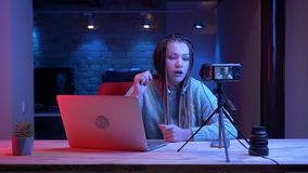 年轻可爱的女性博客作者特写镜头射击有dreadlocks的在打与氖的耳机电子游戏 股票视频