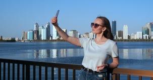 年轻可爱的女性室外画象做selfie的时髦的成套装备的 电话照相机POV 股票录像