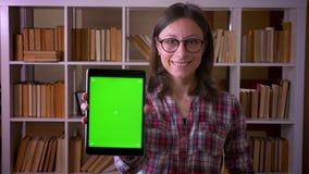 年轻可爱的女生特写镜头射击玻璃的使用片剂和显示对照相机微笑的绿色屏幕 股票录像