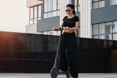 年轻可爱的妇女乘坐的electrick踢滑行车在现代都市风景 免版税库存图片