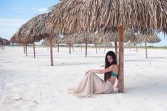 年轻可爱的妇女在度假在海的,坐沙子在秸杆伞下 免版税库存图片