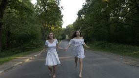 年轻可爱的妇女在跑在森林乡下公路的白色穿戴了赤脚握手- 股票录像