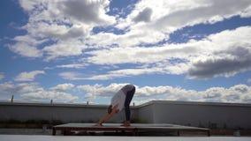 年轻可爱的妇女实践瑜伽,站立向前弯锻炼 股票视频
