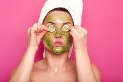 年轻可爱的妇女室内射击有绿色面具的在她的把黄瓜放的部分面孔在她的眼睛上,推出她的嘴唇, 免版税库存图片
