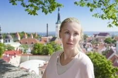 年轻可爱的妇女敬佩老城市的房子屋顶从观察台的 塔林 爱沙尼亚 免版税库存照片