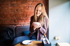 年轻可爱的妇女有一个咖啡休息,坐在与美好的内部的咖啡馆 免版税库存照片