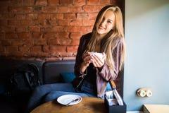 年轻可爱的妇女有一个咖啡休息,坐在与美好的内部的咖啡馆 库存图片