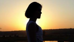 年轻可爱的妇女注视着浪漫遥远精采日落在Slo Mo 股票录像